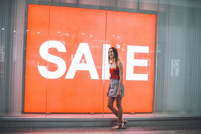 Žena stojaca pred výkladom s veľkým nápisom SALE