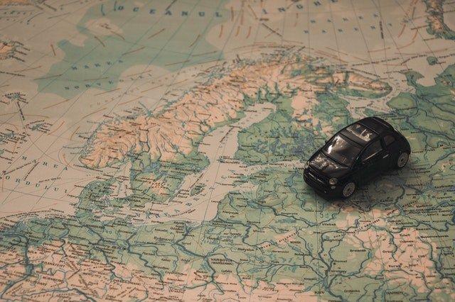 Malé čierne auto položené na mape