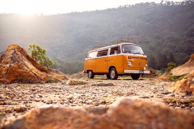 Žltá dodávka zaparkovaná medzi skalami pod lesom