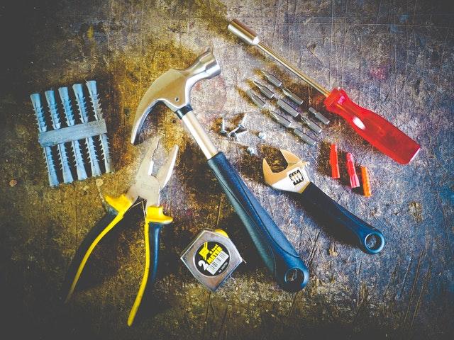 Skrutkovač, kladivo, kliešte, hmoždinky a meter na stole