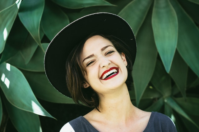 Usmiata žena s červenými perami, v čiernom klobúku pred zelenými listami