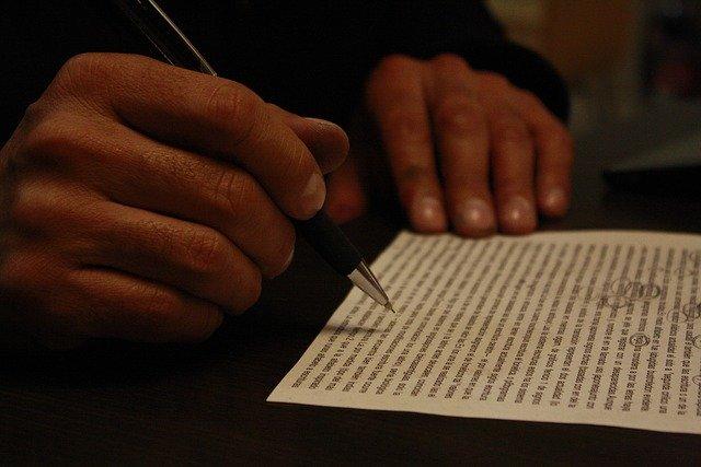 Človek krúžkuje perom chyby na papieri s dlhým textom.jpg